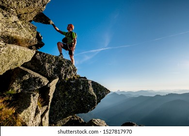 Climber in Austrian Alps ascending the rocky ridge
