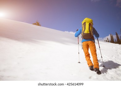 Climber with backpack climbs up a snow mountain.
