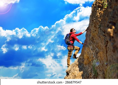 climber with backpack hanging on the rock