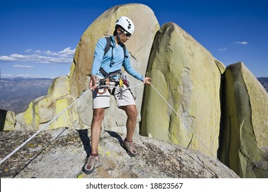 Climber beginning her descent from the summit of a rock spire in The Sierra Nevada Mountains, California, on a summer day.