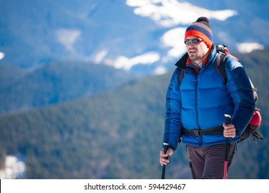 Climber in a blue jacket in the background of mountain, a man with a backpack makes climbing in the winter.