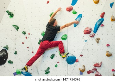 Climber in a boulder gym. Man climbing bouldering problem. Colorful volumes and holds on a white wall.