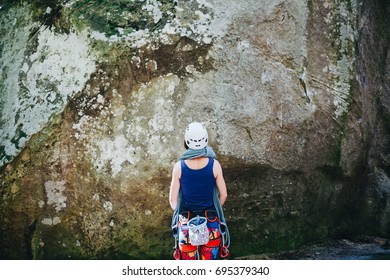 Climber in climbing equipment with rope standing in front of a stone rock and preparing to climb