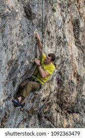 A climber in climbing gear scrambles up the rock with hard emotions on face