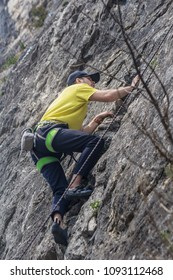 A climber in climbing gear scrambles up the rock