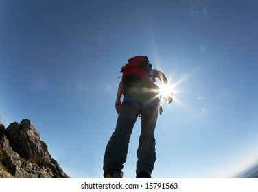 Climber, with climbing gears, standing on a stone at the top of his route, over a deep blue sky.