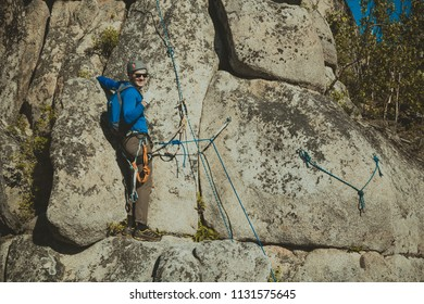 "A climber climbing a rock poses for a photographer and shows the gesture ""horns"" or ""that rocks"" with his fingers"