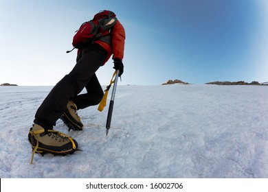 Climber climbing a steep route on a icy slope, italian Alps, Europe.