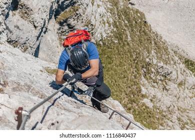 A climber climbing via ferrata. Adventure extreme ascent of an alpine rock wall. Summer mountain sport adventure. Man climbing ferrata.