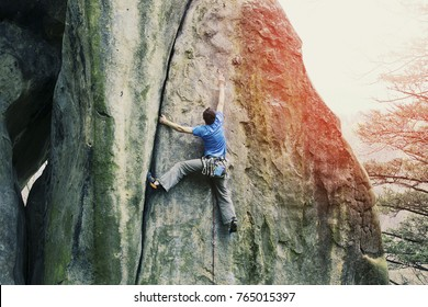 A climber climbs an ascent to a cliff.