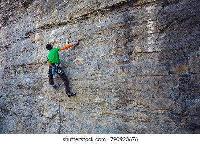The climber climbs on a natural relief. A strong man goes in for sports. Active lifestyle. Athlete on a rock.