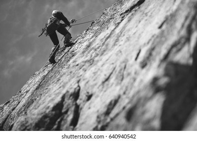 Climber climbs on the rock wall. Climbing gear. Climbing equipment. Black and white.