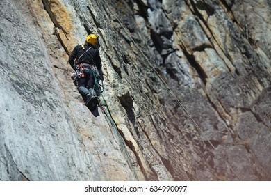 Climber climbs up the rock wall. Climbing gear and equipment.