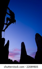 A climber clings to the side of an overhanging rock in The Sierra Nevada Mountains, California.