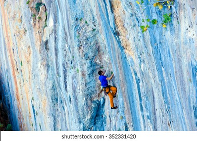 Climber conquering Rock Wall with colorful Texture of orange grey and blue Stripes