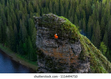climber descends from the top of a steep cliff above the river (rock Devil's Finger on the river Usva, Middle Urals)