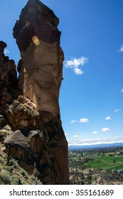 Climber dwarfed by the overhanging  cliff of Monkey Face, Smith Rock State Park, Central Oregon
