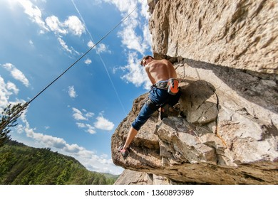Climber Extreme climbs a rock on a rope with the top insurance, against the blue sky, bottom view