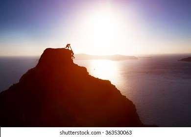 Climber giving hand and helping his friend to reach the top of the mountain. Help, support, assistance, teamwork in a dangerous situation concepts