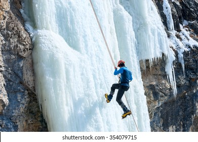 Climber going down the rope with a frozen waterfall