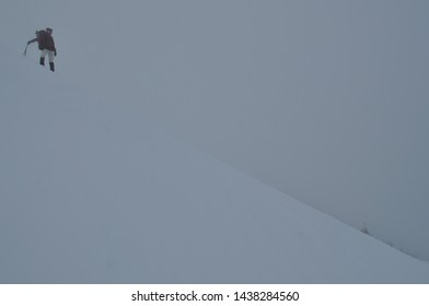 climber going down to a steep snowy abyss. Winter storm in Carpathian Mountain.Mountaineer climbing a steep route on a icy slope