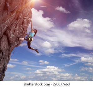 Climber hanging on her hand. Elegant female athlete hanging at top of dangerous peak equipped with gear rope harness blue sky and terrific clouds on background and sunbeams shining from above