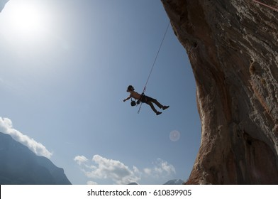 Climber hanging on a rope under the rocks