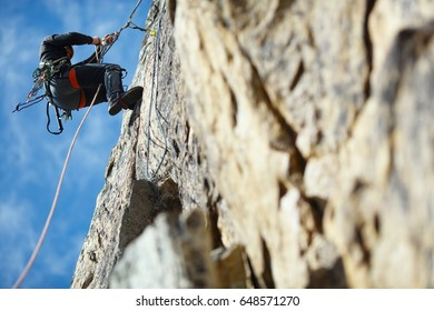 The climber is hanging on a safety rope on a rock wall.