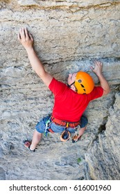 Climber in a helmet climbs to the top of the mountain. Sport activities in nature.