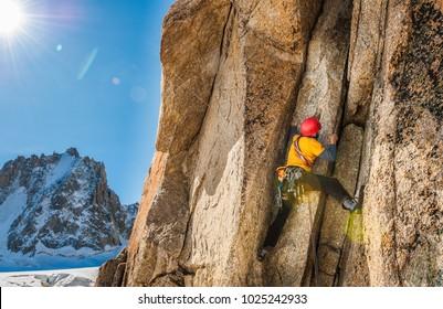 Climber in high mountain climbing rock chimney