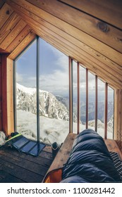Climber and hiker equipment inside a wooden mountain shelter. View from a bivouac, sleeping bag, boots and a solar panel in a mountain shelter in the alpine landscape of Kamnik Savinja alps near Skuta