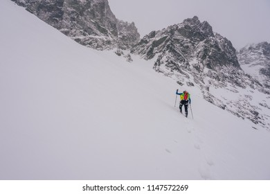 Climber or hiker on an adventure winter ascent in misty winter alpine mountain landscape. Winter trekking, approach to a climb. Snow walking with poles or sticks.