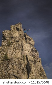 A climber holds a rope over his head posing to the photographer from the top of the cliff. Dark blue sky on background