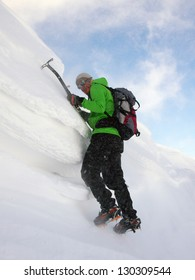 A climber with ice axes and crampons climbing a snow cornice in very high wind conditions. The wind is blowing snow and ice particles all over the climber almost covering him