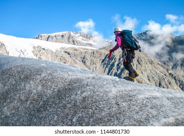 A climber makers her way up the Fox Glacier with typical mountaineering safety gear. South island of New Zealand.
