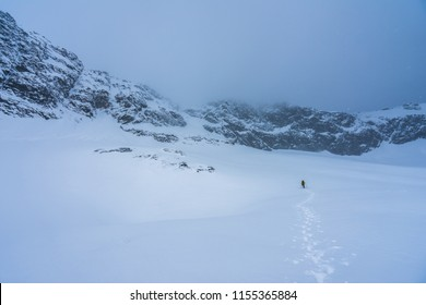 A climber on an adventure ascent in the alpine like winter montain landscape. Snow and ice covered high peak, rock face. Alpinist climbing in winter mountains of High Tatra.