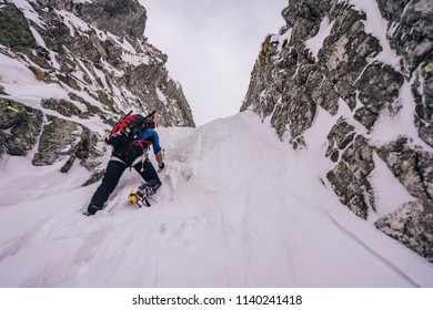 Climber on an adventure mountain ascent, climbing on ice and snow. Extreme alpinism, alpine climbing and mountaineering. Rocks, snow and ice, dangerous sport activity in alpine landscape.