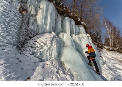 Climber on icefall climbs, twists ice screws, drill icicles