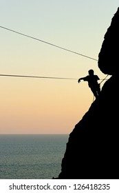 climber on a rock preparing the rope for highlining against the sea at sunset