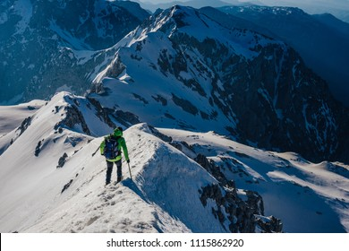 Climber on a sharp snow and rock ridge in the winter alpine landscape. Adventure climb, mountaineering in winter Kamnik Savinja alps, Slovenia. Ascent or descent of a peak or summit in the alps.