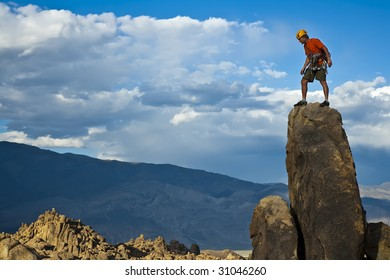 Climber on the summit of a rock spire after a successful ascent.