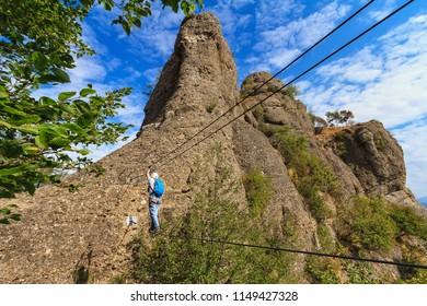 Climber on the suspension bridge in Deanna Orlandini via ferrata, Rocche del Reopasso, Liguria, Italy
