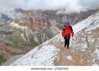"""Climber on top section of via ferrata """"Lipella"""" , Tofana massif, Dolomite Alps, Italy"""