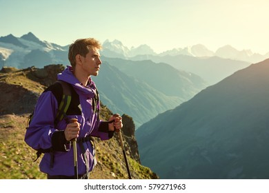 climber on trail in the mountains. a man with a backpack in a hike
