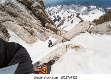 Climber on a vertical peak rappel his friend with crampons and ice axes on a vertical ice wall