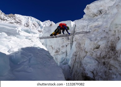 Climber passes a crack in the glacier on the ladder on the way to Mount Everest, Himalayas, Nepal