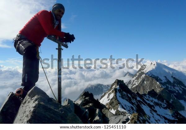 Climber posing at Lagginhorn mountain's summit in the Alps, Switzerland