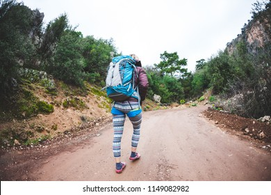 The climber is preparing for the ascent. A woman in a safety system and with a backpack approaches the climbing route. Mountain climbing. Fitness in nature. Mountaineer is walking along a stony path.