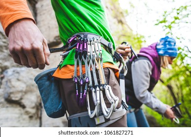 The climber is preparing for the route. Climbing equipment on the safety system. Carbines and quickdraw.