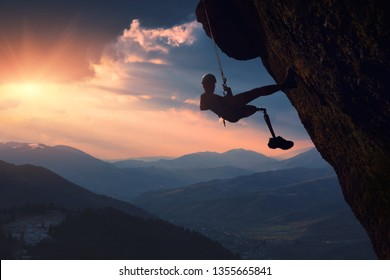 The climber with prothesis on a cliff in a mountain valley at sunset. Active people with disabilities.